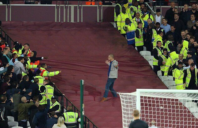 IS THIS HOW IT STARTED? A CHELSEA FAN SOMEHOW EVADES STEWARDS  AND MAKES HIS WAY TOWARDS THE IRONS SECTION BAITING THEM AS HE GOES BEFORE QUICKLY DOING AN ABOUT TURN AFTER THIS IMAGE WAS TAKEN. IDIOCY OF THE HIGHEST POSSIBLE ORDER.